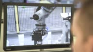 Employees monitor robotic arms manufactured by Kuka AG performing mock operations on handling contaminated barrels of sludge and debris at the...