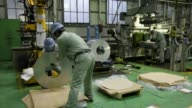 Employees operate machinery as they stack coils of slit aluminum strips for packaging on the production line at Tokiwa Koutai Cos aluminum processing...