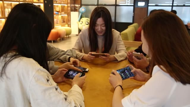 Employees play mobile games on smartphones in the cafeteria at the Netmarble Games Corp headquarters in Seoul South Korea on Friday April 14 2017