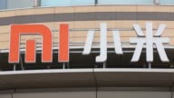 Employees stand next to a Xiaomi Corp logo displayed outside the companys headquarters in Beijing China on Friday Sept 12 Zoom out and into the...