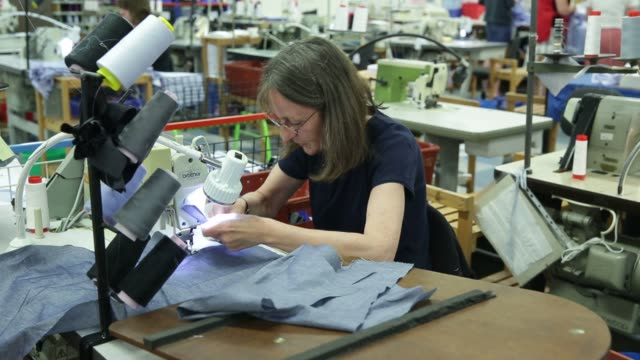 Employees use sewing machines to sew together shirts and fabrics at Drake's factory in Chard UK on Tuesday July 7 2015 Shots shots of woman putting...