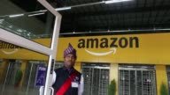 Employees walk through the warehouse floor of the Amazoncom Inc fulfillment center in Hyderabad India on Thursday Sept 7 A security guard stands at...