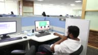 Employees work at the Thinkand Learn Pvt office in Bengaluru India on Wednesday April 5 Employees gather at a computer in the Thinkand Learn Pvt...