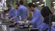 Employees work on the assembly of Xvision digital receiver units at the Maadiran Group electronics distribution and manufacturing plant in Hashtgerd...