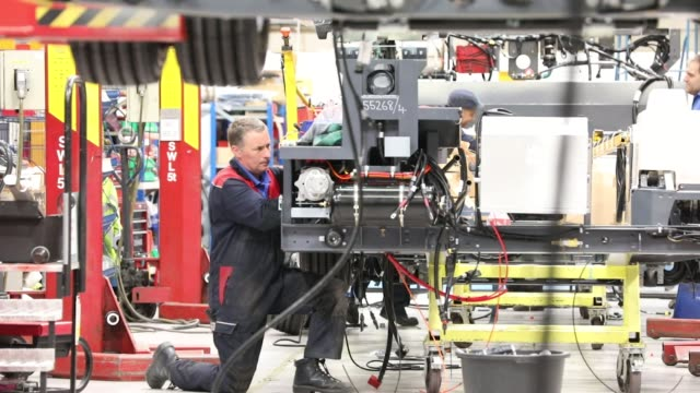 Employees work on the engine section of an Enviro 200 bus at the Alexander Dennis Ltd factory in Guildford UK on Monday Sept 11 An employee works on...