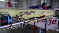 Employees work on the wing of a Bombardier Inc Q400 NextGen passenger aircraft undergoing maintenance at the Air Works Engineering Pvt hangar in...