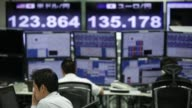 WS Employees work while monitors display the exchange rate of the yen against the US dollar top left and the euro top center at a foreign exchange...