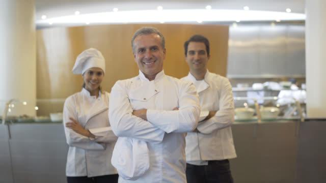 Mündige Chef steht in der Front mit seinem Sous-chefs