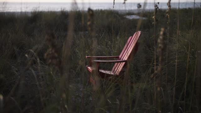 Empty adirondack chair on beach