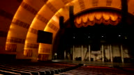 Empty auditorium behind rows of seats stage raised curtain proscenium arch w/ attached speakers monitors