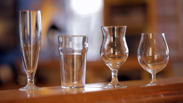 Empty beer glasses of different shapes on a bar