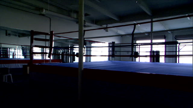 Pan ws dimly lit empty boxing ring in garage