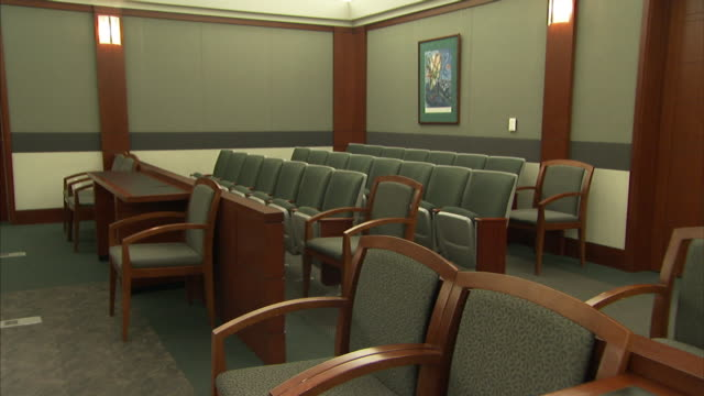 Empty chairs fill a courtroom.