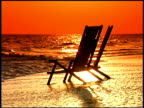Empty chairs on seashore at sunset