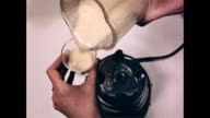 Empty electric blender sitting on counter top / female hand pours contents of a small tin can into blender / creamy offwhite liquid in blender /...