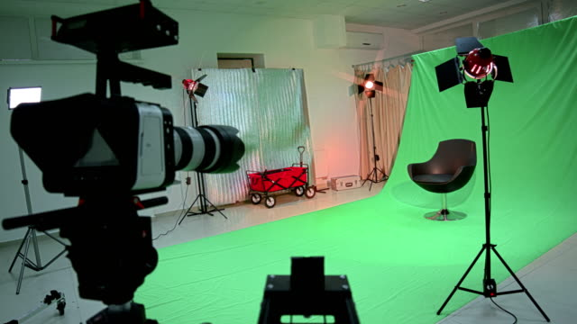 Empty film studio with photo equipment and chroma key backdrop
