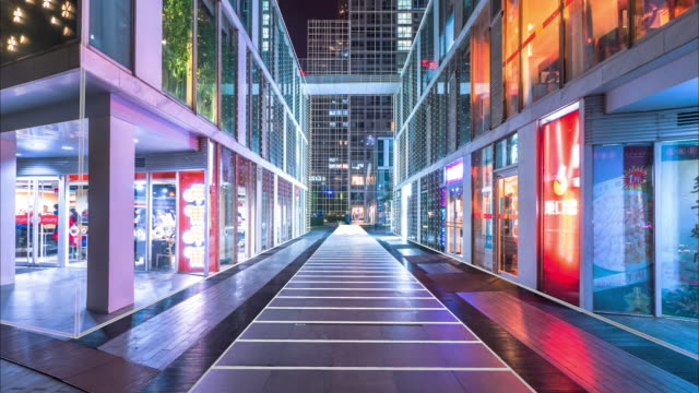 empty footpath between modern business buildings at night. time lapse