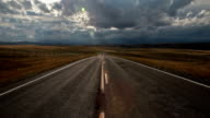 POV of empty Highway with dramatic clouds on prairie and sun moving across landscape.