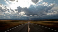 POV of empty Highway with dramatic clouds.