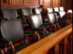 ZO Empty jury box seats behind wooden barrier Jury duty verdict trial law judicial guilty not guilty innocent deliberation