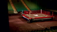 Empty lighted arena floor to boxing ring w/ overhead spotlights amp colored seating lighting on