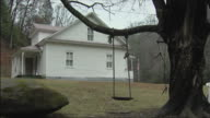 MS empty swing hanging from tree in yard of white house / Bob White, West Virginia