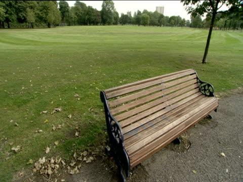 Empty wooden bench in urban parkland Victoria Park London