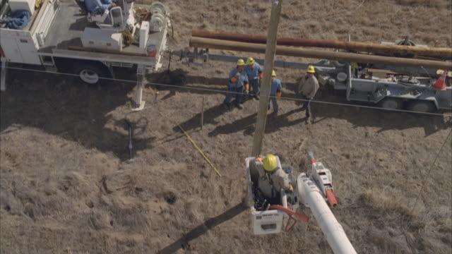 MS AERIAL Energy worker raising in cherry picker to adjust powerline / Hooker, OK, USA