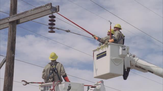 MS AERIAL Energy workers adjusting powerline / Hooker, OK, USA