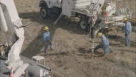 MS AERIAL Energy workers drilling hole to errect power line pole / Hooker, OK, USA