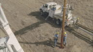WS AERIAL Energy workers planting power line pole into ground / Hooker, OK, USA