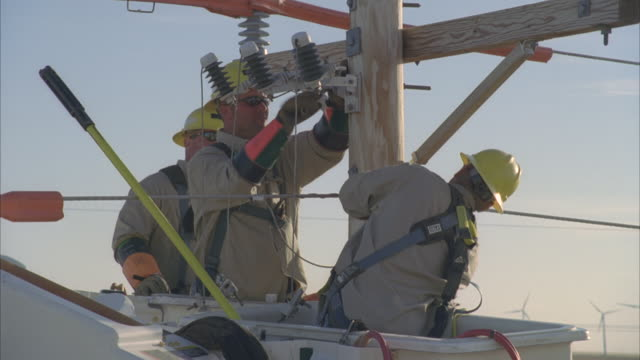 CU AERIAL Energy workers working on power lines, Wind farm in background / Hooker, OK, USA