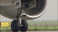 CU Engine and landing gear of commercial jet taxiing on runway / Tokyo, Tokyo Prefecture, Japan