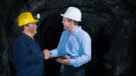 Engineer and miner talking at the mine