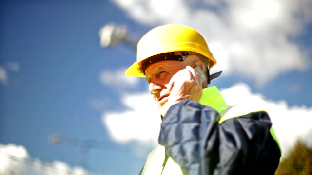 engineer at a construction site talking on the phone.