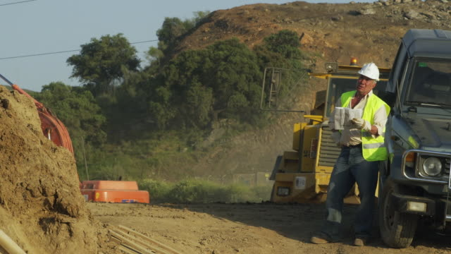 WS Engineer checking plans on construction site with huge dump truck driving background / Malaga, Andalusia, Spain