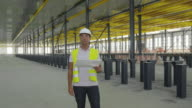 MS engineer holding plan standing in large hangar, looking around ostensible checking things, front view, RED R3D 4K