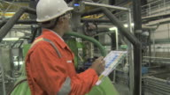 Engineer in factory with clipboard