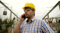Engineer in front power station using phone