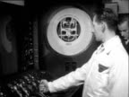 Engineer in white coat opens throttle lever and needle on large gauge behind him rises he pulls lever back and needle on gauge falls again 1950s