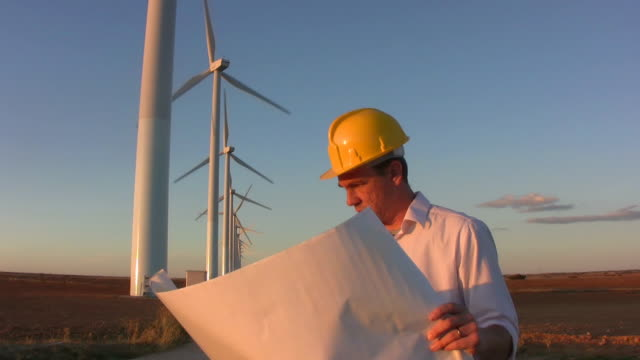 Engineer looks at plans windmills background