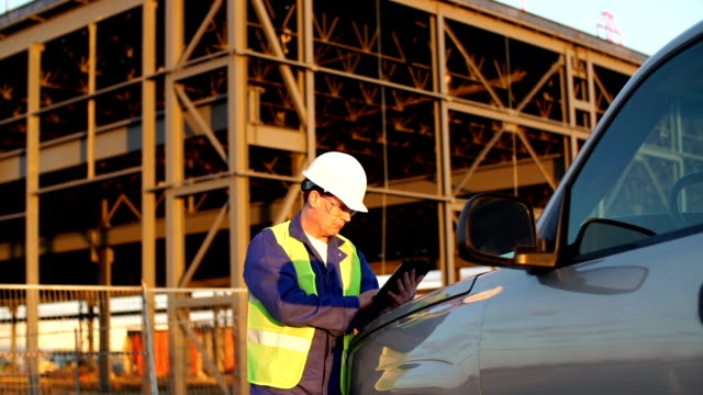 Engineer or job superintendent uses a tablet on construction site