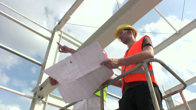 Engineer pointing and reviewing Blueprint