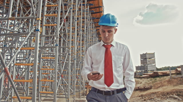 Engineer using a smartphone at the construction site