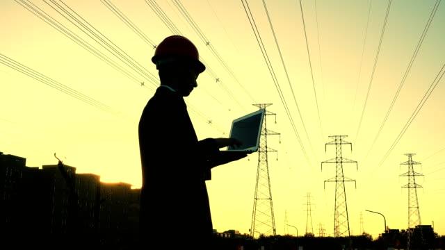 Engineer using laptop at sunset
