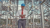 Engineer walking with digital tablet at the construction site