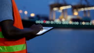 Engineer with tablet at industrial, Cargo container