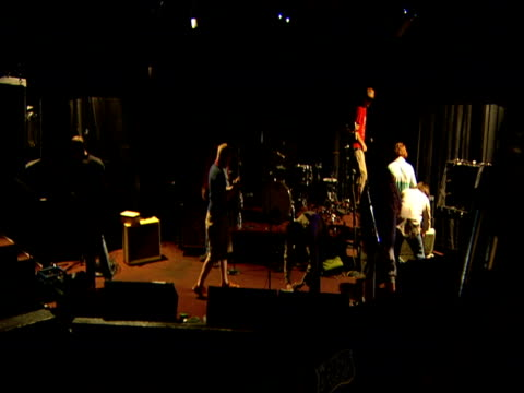 Engineers and musicians set up stage for gig dim light Sunset Strip