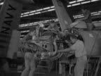 Engineers factory workers working on partially built Grumman F9F Panther fighter jet in hangar 'NAVY' written on wing working on frame of cockpit...