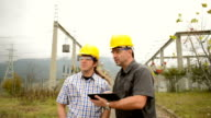 Engineers in front power station using tablet